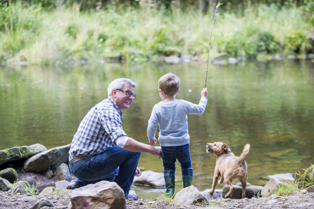 A little boy is playing outdoors, next to the lake with his grandfather.