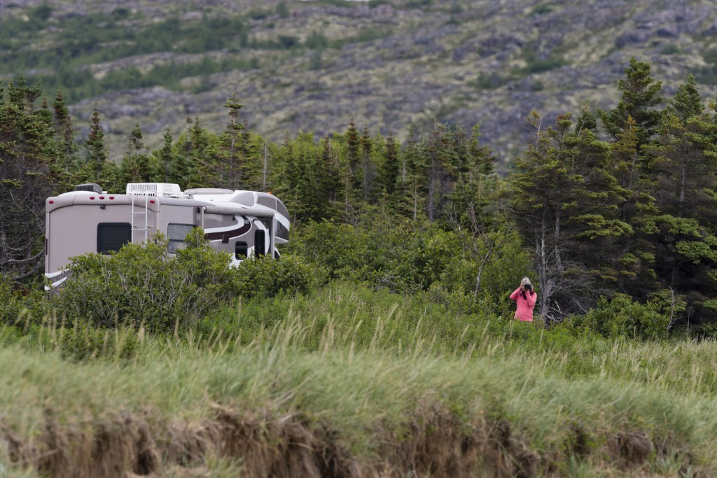 Woman photographing in road trip in Labrador and Newfoundland. Motorhome in Labrador. Camping in nature. Nature photographer.