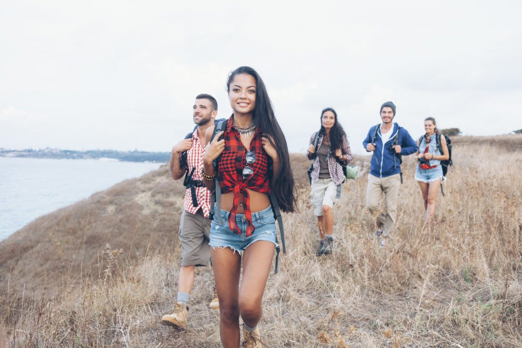 Group of backpackers hiking together at the ocean