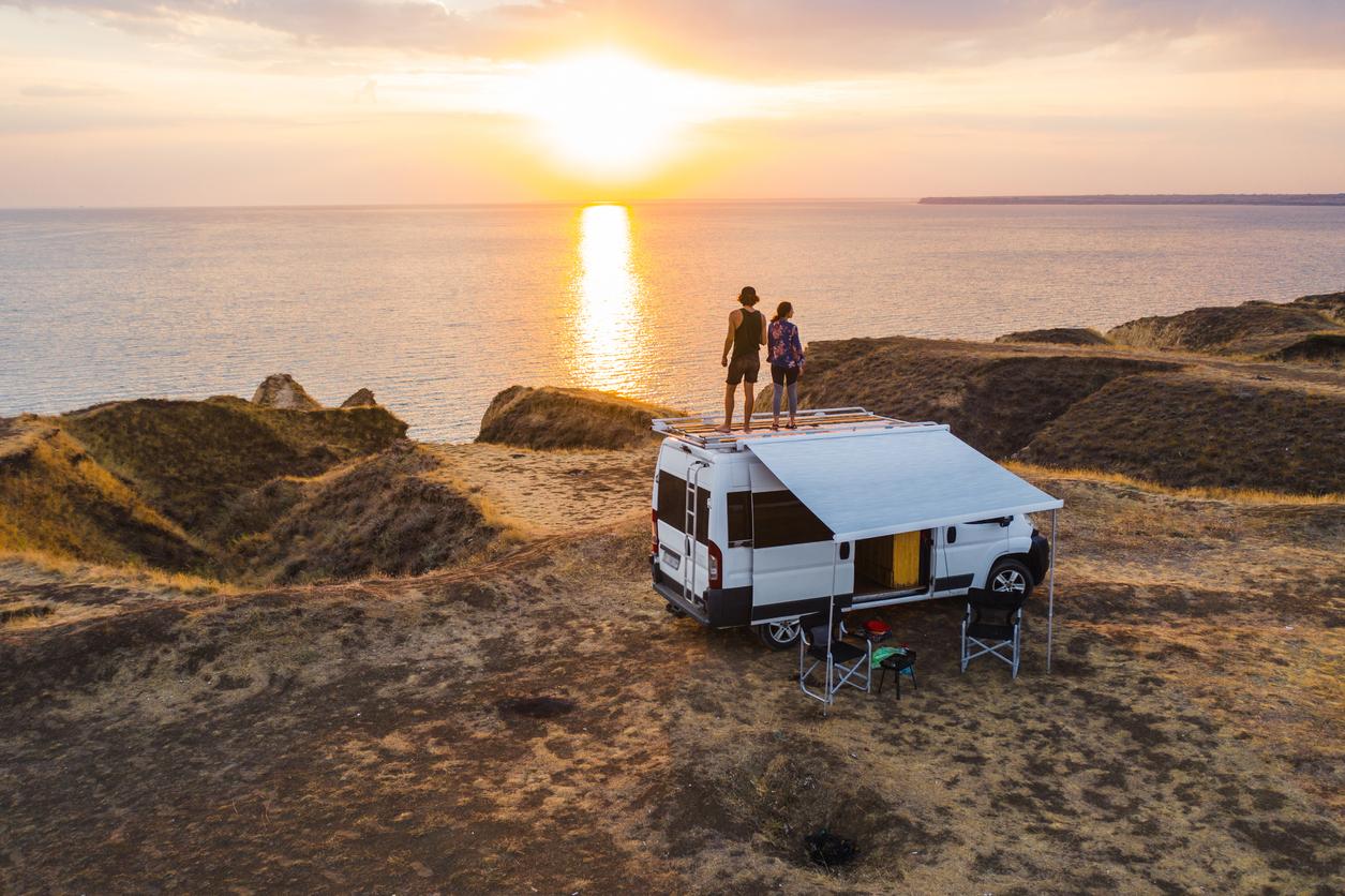 Couple overlooks ocean atop camper van