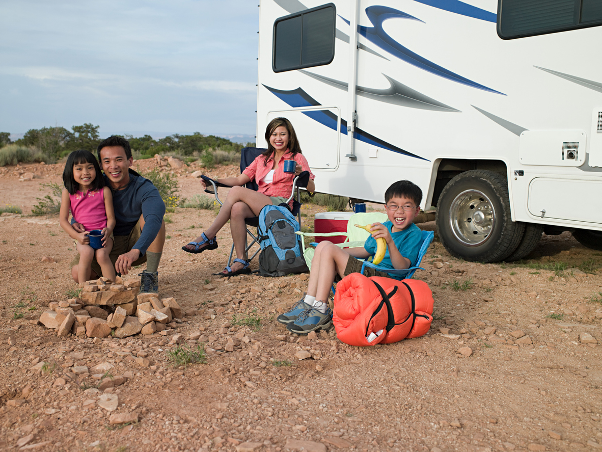 Kids sit outside RV with parents