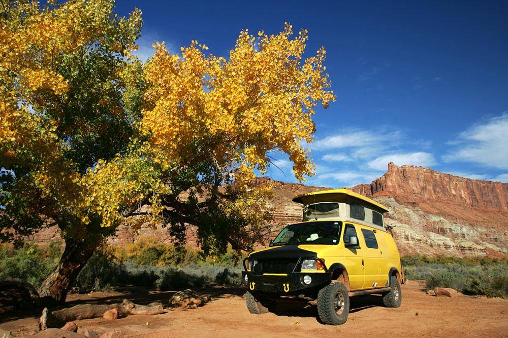 Overland camper van sits among fall trees in a Utah landscape